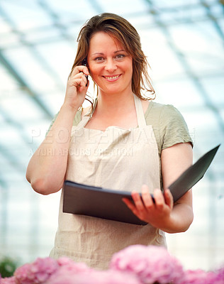 Buy stock photo Happy young female florist speaking on the cellphone while at a greenhouse