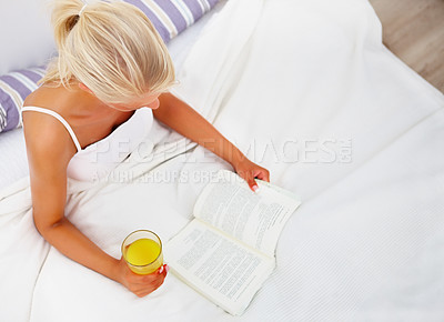 Buy stock photo Top view of a happy young woman reading a book on bed while having juice