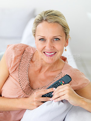 Buy stock photo Portrait of an elderly woman relaxing at home , holding the television remote controller