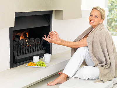 Buy stock photo Portrait of a pretty woman by a fireplace at home