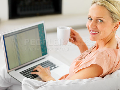 Buy stock photo Portrait of a happy middle aged woman using a laptop at home , having a cup of coffee