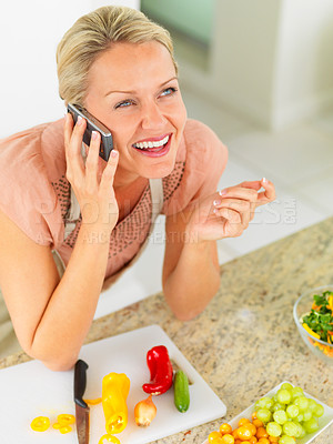Buy stock photo Happy middle woman enjoying a conversation while preparing a salad at home
