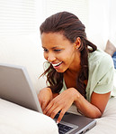 Closeup of an African American woman lying on sofa, using laptop