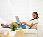 An African American woman working on laptop in the living room