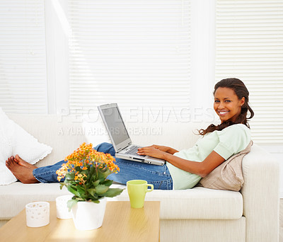 Buy stock photo An African American young woman working on laptop in the living room