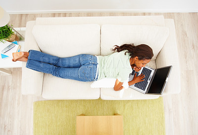 Buy stock photo Top view of an African American woman lying on sofa and working on laptop