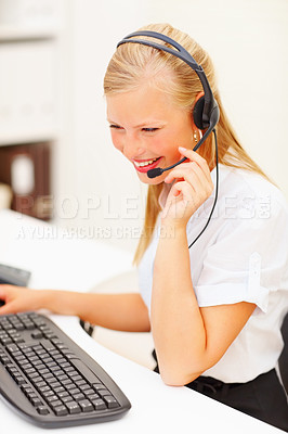 Buy stock photo A woman working on computer and wearing headphones