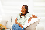 African American female seated on couch and laughing at home
