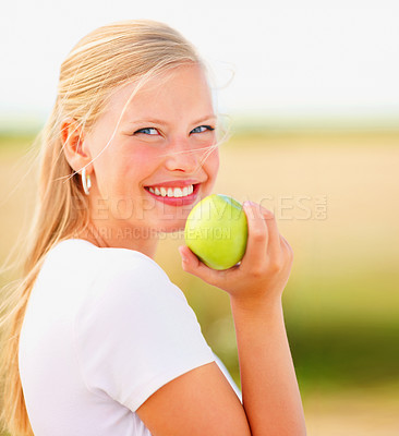 Buy stock photo Closeup portrait of a young blond holding a green apple outdoors