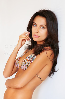 Buy stock photo Portrait of a woman wering a bikini leaning against wall