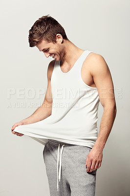 Buy stock photo Studio shot of a casually dressed young man laughing while pulling on his shirt