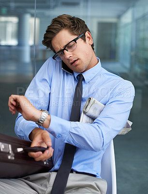 Buy stock photo A busy young entrepreneur checking the time while taking a call