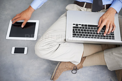 Buy stock photo Top-view of a businessman using his tablet, smartphone and laptop while sitting on the floor