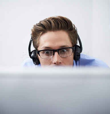 Buy stock photo A businessman wearing a headset looking at his screen with astonishment