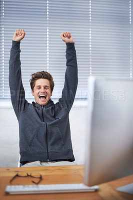 Buy stock photo A handsome young man celebrating at his desk