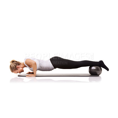 Buy stock photo A young woman doing press-ups while using an exercise ball to raise her legs