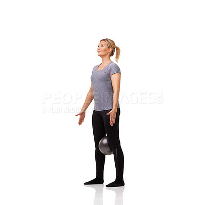 Buy stock photo A pretty young woman working out with an exercise ball while isolated on a white background