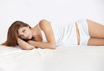 Buy stock photo Portrait of a stunning young woman lying in bed wearing a sleepshirt and underwear