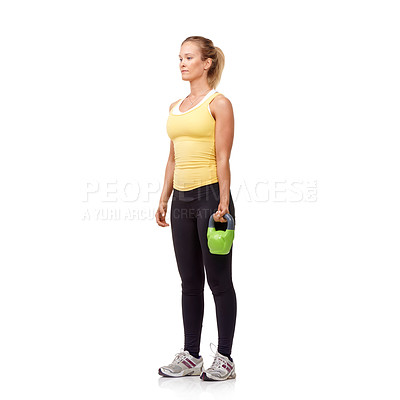 Buy stock photo A pretty young woman standing ready with a kettlebell while isolated on white