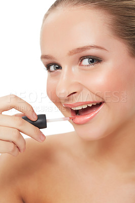 Buy stock photo A stunning young woman applying lipgloss to her luscious lips while isolated on white