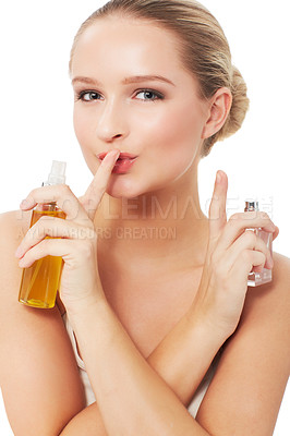 Buy stock photo A gorgeous young woman with a finger to her lips while holding her beauty products