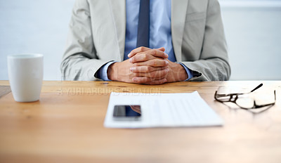 Buy stock photo Cropped image of a businessman sitting with hands clasped and paperwork in front of him