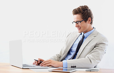 Buy stock photo A smiling young businessman working on his laptop in the office