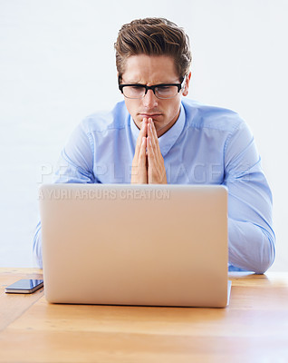 Buy stock photo A handsome young businessman focused on his laptop