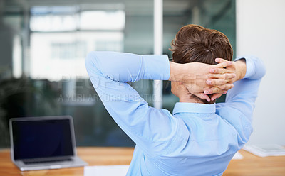 Buy stock photo A satisfied young businessman leaning back with his hands behind his head - rear view