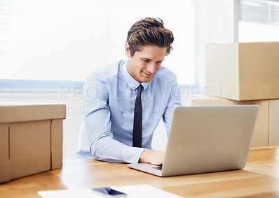 Buy stock photo A young businessman working on his laptop after moving offices