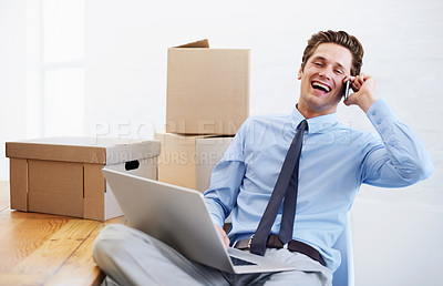 Buy stock photo An excited businessman on his cellphone after moving offices
