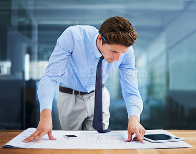Buy stock photo A young architect examining his blueprints in his office while at his desk