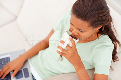 Buy stock photo Top view of a young African American lady working on a laptop and having cup of tea