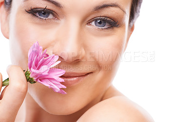 Buy stock photo A lovely young woman smiling at the camera while sniffing a pink flower