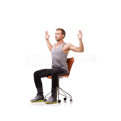 Buy stock photo A handsome young man wearing gym clothes and stretching while seated in an office chair against a white background