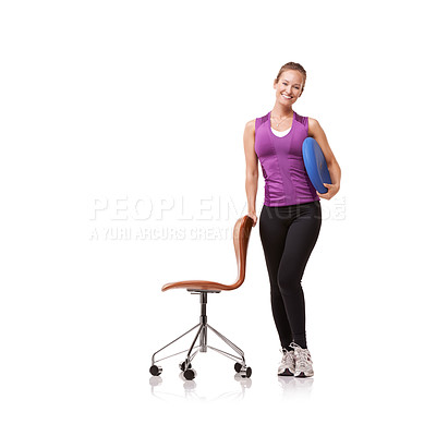 Buy stock photo A beautiful young woman, standing next to a chair and holding a balance cushion under her arm against a white background