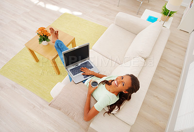 Buy stock photo Top view of cheerful African American girl working on laptop, having cup of coffee