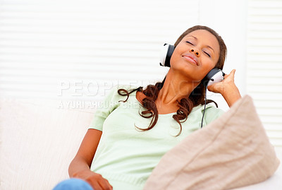 Buy stock photo Young African American girl enjoying music on the headphones while at home