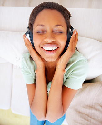 Buy stock photo Top view of a young African American woman listening to music on the headphones