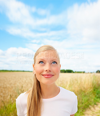 Buy stock photo Beautiful young woman laughing and looking up at copy space at a field