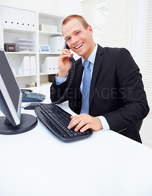 Buy stock photo Portrait of a smiling young business man communicating on telephone while using computer