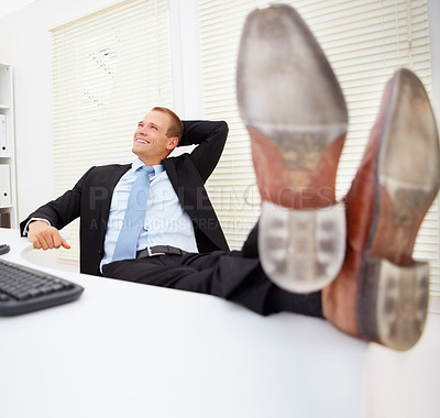 Buy stock photo Happy young business man sitting in the office with legs over table