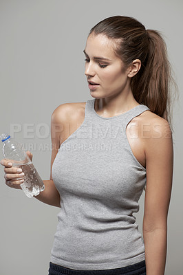 Buy stock photo Studio shot of a young woman drinking water from a bottle