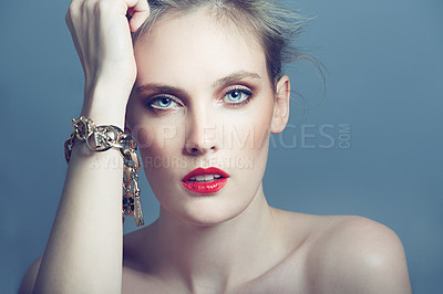 Buy stock photo Head and shoulders portrait of a beautiful young woman wearing a bracelet