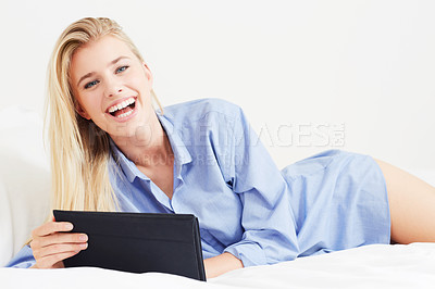 Buy stock photo A beautiful young blonde woman lying in bed with her digital tablet