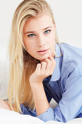 Buy stock photo A beautiful young blonde woman wearing a blue shirt with her chin on her hand - portrait