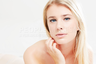 Buy stock photo A beautiful young blonde woman with bare shoulders looking at the camera and touching her cheek