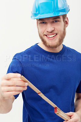 Buy stock photo Portrait of a happy young man wearing a hardhat and using a carpenter's ruler
