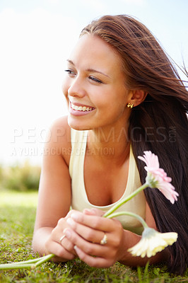 Buy stock photo Cute young female lying on grass field while holding a flower