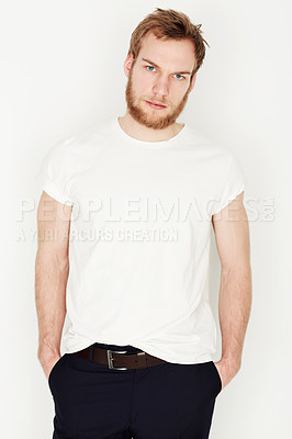 Buy stock photo Portrait of a young man standing against a wall with his hands in his pockets